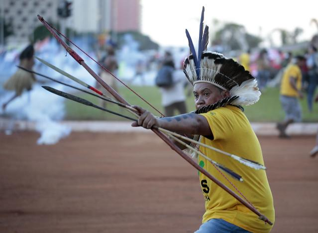 A native Brazilian aims an arrow at riot police who fired tear gas to prevent a group of Indians from approaching the Mane Garrincha soccer stadium during a demonstration in Brasilia May 27, 2014. Indigenous people from different tribes protested against the government's Indian policy and the costs of the 2014 World Cup. REUTERS/Joedson Alves (BRAZIL - Tags: SPORT SOCCER WORLD CUP CIVIL UNREST POLITICS)