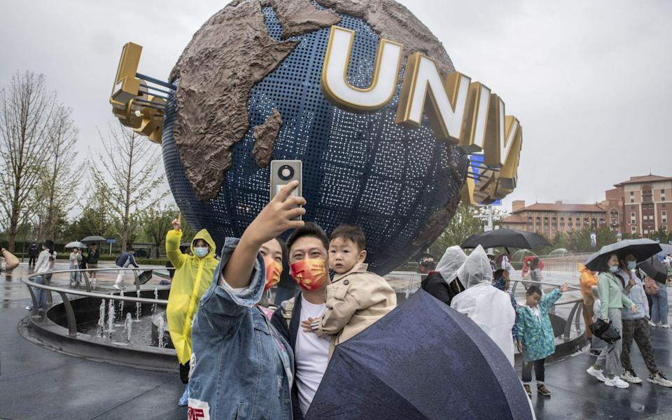 A family wearing face masks take selfies at the entrance of the Universal Studios Beijing theme park on 20 September 2021 - Gilles Sabrie/Bloomberg