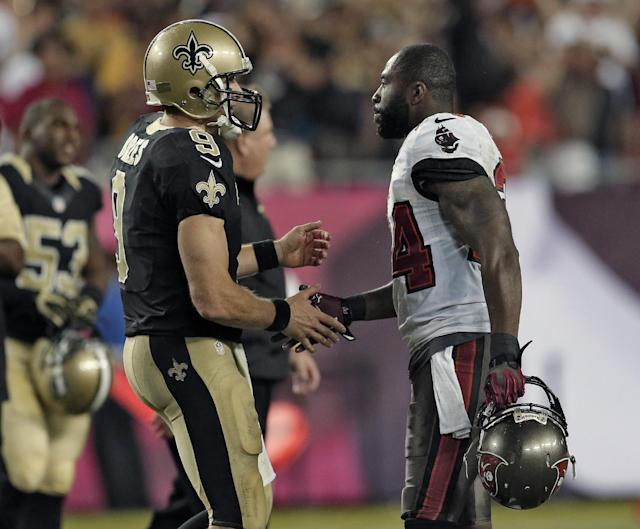 New Orleans Saints quarterback Drew Brees (9) shakes hands with Tampa Bay Buccaneers cornerback Darrelle Revis (24) after the Saints defeated the Buccaneers 16-14 during an NFL football game Sunday, Sept. 15, 2013, in Tampa, Fla. (AP Photo/Chris O'Meara)