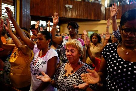 People react during a religious ceremony where victims of the Boeing 737 plane crash were remembered at a church in Havana