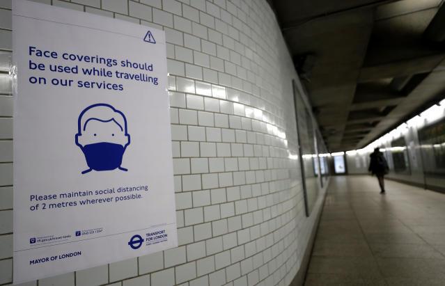 A sign advises travellers to wear face coverings at Westminster Station in London. (PA)