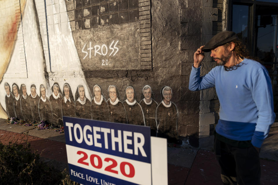 Artist Edward Stross stands next the mural he painted to honor the 13 nuns who died at a local convent from COVID-19, at his studio in Roseville, Mich., Saturday, Oct. 31, 2020. As the coronavirus crisis surges to more than nine million infections and 230,000 dead, the election for many is a referendum on how Trump has handled the pandemic. In the final days of the campaign, he has continued to downplay the toll it has taken, and many of his supporters say they find no fault in his response. (AP Photo/David Goldman)