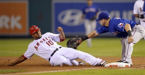 Los Angeles Angels' Vernon Wells, left, is tagged out at first by Texas Rangers first baseman Mitch Moreland after trying to get back to first when a long fly ball by Alberto Callaspo was caught during the second inning of their baseball game, Wednesday, Sept. 19, 2012, in Anaheim, Calif. (AP Photo/Mark J. Terrill)