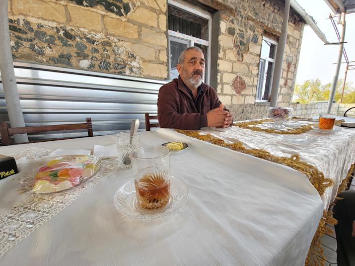 Nizami Aghayev, 56, who lost three members of his family in a missile strike on Ganja, Azerbaijan, sits at a table outdoors.