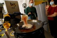 Chef Maria Munoz watches as a robot created by Spanish companies br5 and Mimcook makes paella during a demonstration at a warehouse in San Fernando de Henares
