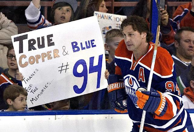 Fans hold up signs for Edmonton Oilers' Ryan Smyth (94) as he skates during warm up for his last game before his retirement from NHL hockey, in Edmonton, Alberta, on Saturday April 12, 2014. (AP Photo/The Canadian Press, Jason Franson)