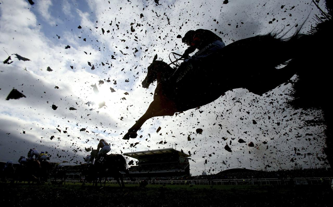 <p>Debris flies as runners and riders clear a fence during day one of the Grand National Festival at Aintree Racecourse, England, Thursday April 6, 2017. (Niall Carson/PA via AP) </p>