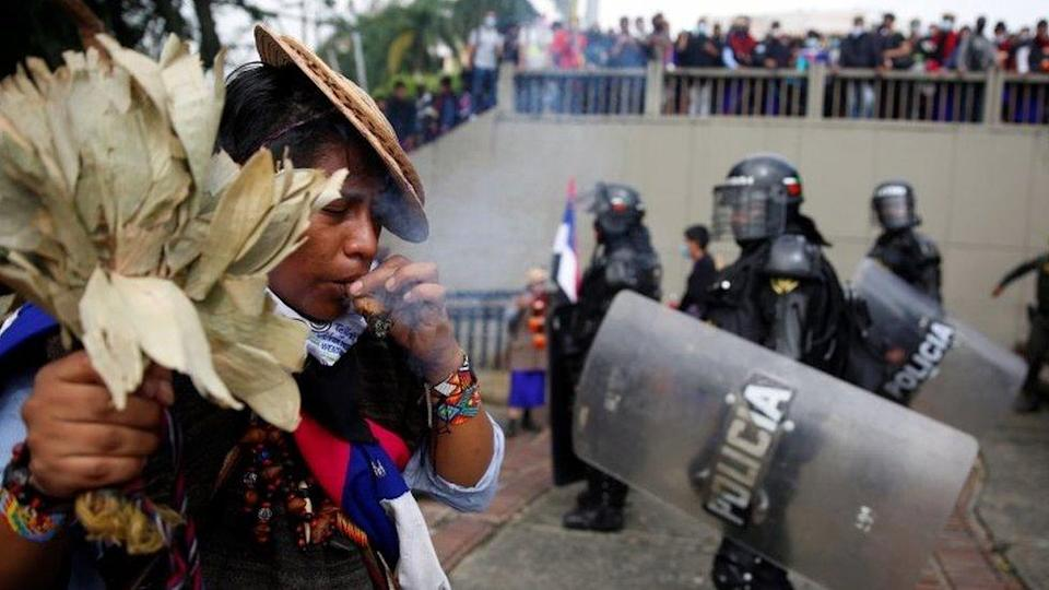 """An indigenous person performs a ritual in front of the authorities after protesters knocked down the statue of the founder of the city, Spanish conqueror Sebastian de Belalcazar, during the protests against the tax reform called by the workers"""" centrals in Cali, Colombia, 28 April 2021"""