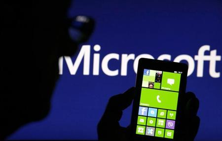 A man is silhouetted against a video screen with the Microsoft logo in the background as he poses with a Nokia Lumia 820 smartphone in this photo illustration taken in the central Bosnian town of Zenica September 3, 2013.