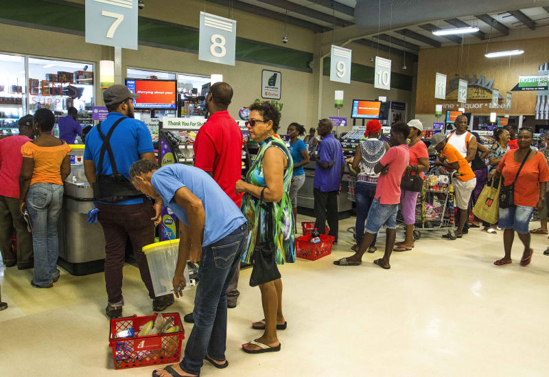 Residents stand in line at a grocery store as they prepare for the arrival of Tropical Storm Dorian, in Bridgetown, Barbados, Monday, Aug. 26, 2019. Much of the eastern Caribbean island of Barbados shut down on Monday as Dorian approached the region and gathered strength, threatening to turn into a small hurricane that forecasters said could affect the northern Windward islands and Puerto Rico in upcoming days. (AP Photo/Chris Brandis)