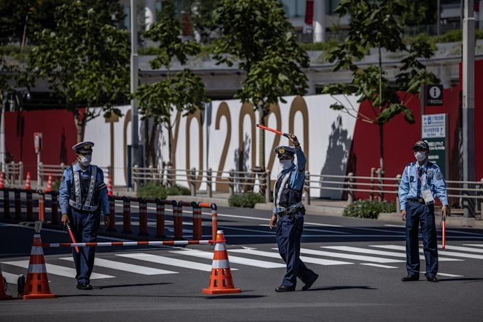 Police officers guard a road next to the Tokyo Olympic stadium, July 21, 2021 in Tokyo, Japan. / Credit: Carl Court/Getty