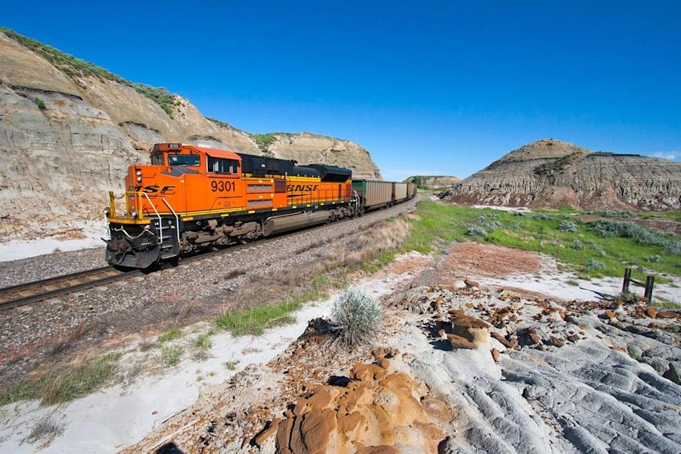 A BNSF Railway locomotive pushes on the rear of an empty coal train in the North Dakota Badlands