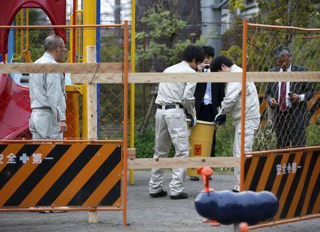 Workers of Tokyo's Toshima ward office carry away a container holding a fragment of an unknown object after it was dug up from the ground near playground equipment at a park in Toshima ward, Tokyo April 24, 2015. REUTERS/Toru Hanai