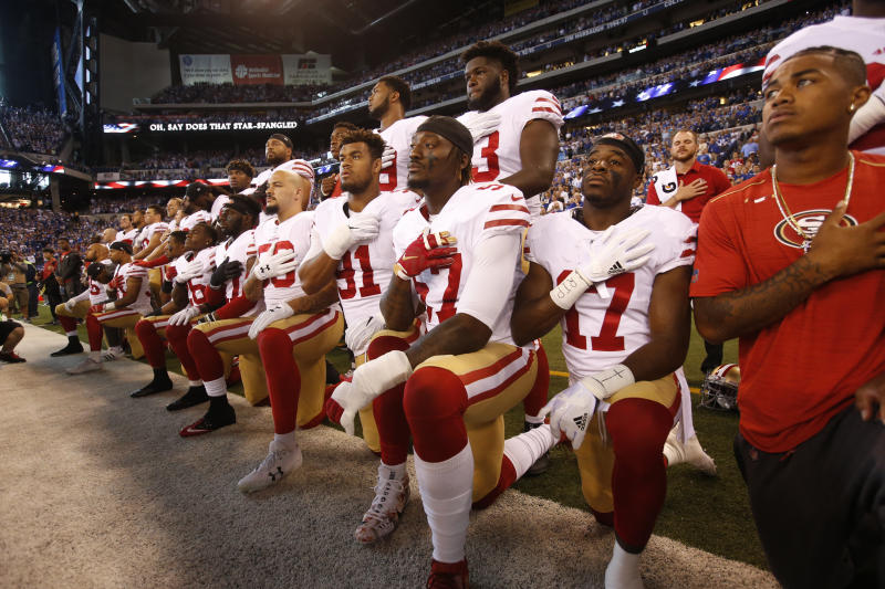 The San Francisco 49ers kneel and stand together while the national anthem plays prior to their game against the Indianapolis Colts on Oct. 8. (Michael Zagaris via Getty Images)