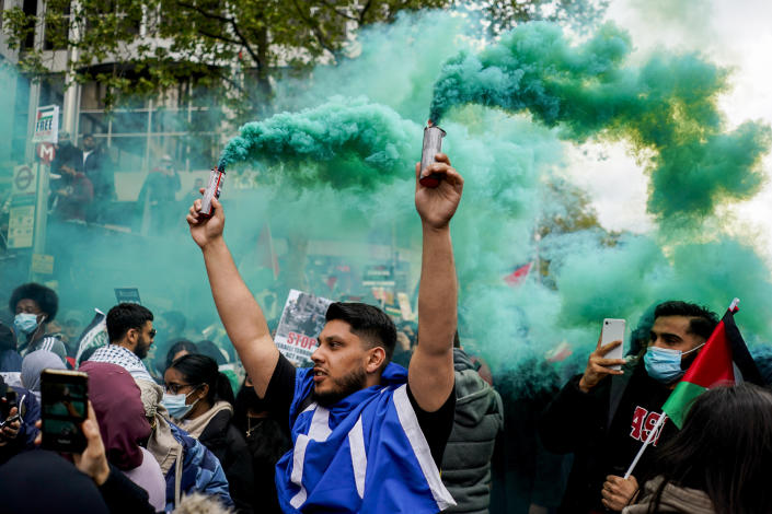 A demonstrator holds two flares during a march in solidarity with the Palestinian people amid the ongoing conflict with Israel, during a demonstration in London, Saturday, May 15, 2021. (AP Photo/Alberto Pezzali)