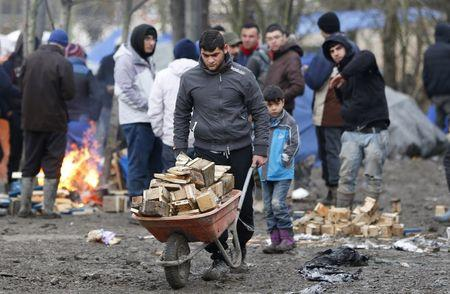 A migrant pushes a wheelbarrow in a muddy field at a camp of makeshift shelters called the Grande Synthe jungle, near Calais