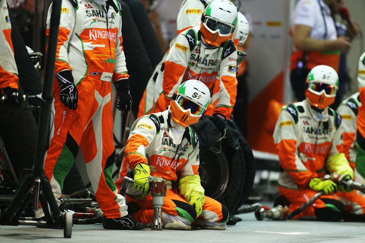 SINGAPORE - SEPTEMBER 23:  Force India mechanics prepare for a pitstop during the Singapore Formula One Grand Prix at the Marina Bay Street Circuit on September 23, 2012 in Singapore, Singapore.  (Photo by Mark Thompson/Getty Images)