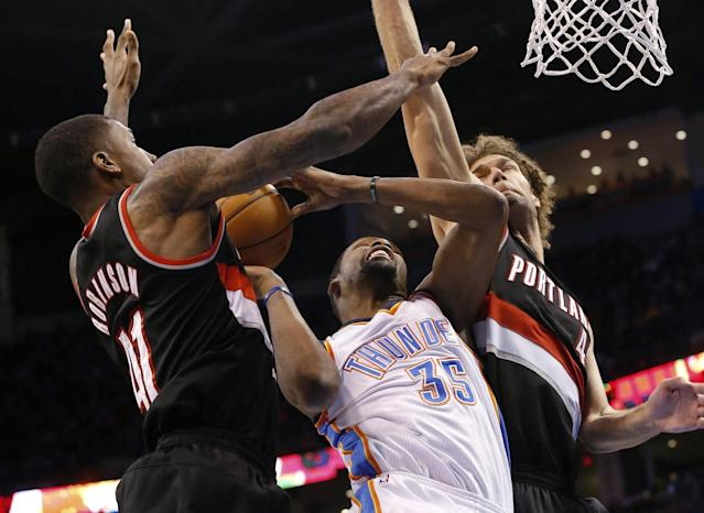 Oklahoma City Thunder forward Kevin Durant (35) shoots between Portland Trail Blazers forward Thomas Robinson, left, and center Robin Lopez, right, in the fourth quarter of an NBA basketball game in Oklahoma City, Tuesday, Jan. 21, 2014. Oklahoma City won 105-97. (AP Photo/Sue Ogrocki)