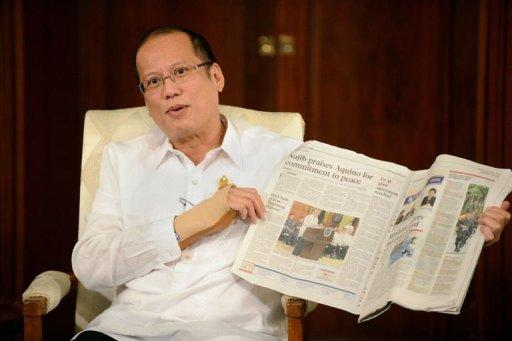Philippine President Benigno Aquino shows a newspaper with a story about the resolution