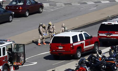 Emergency workers in hazmat suits work in a Pentagon parking lot after a woman who recently traveled to Africa vomited there, in Washington October 17, 2014. REUTERS/Kevin Lamarque