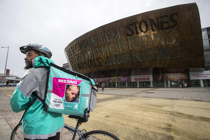 A Deliveroo driver with a missing person poster on their backpack