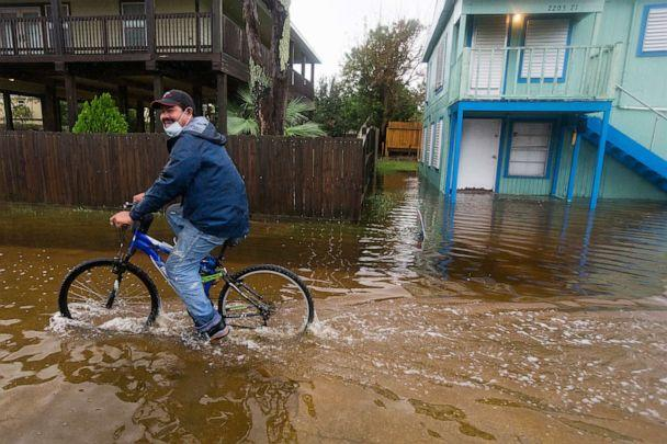 PHOTO: Rafael Juarez rides his bicycle through a street flooded by Tropical Storm Beta as he makes his way home from the store, Sept. 21, 2020, in Galveston, Texas. (Brett Coomer/AP)
