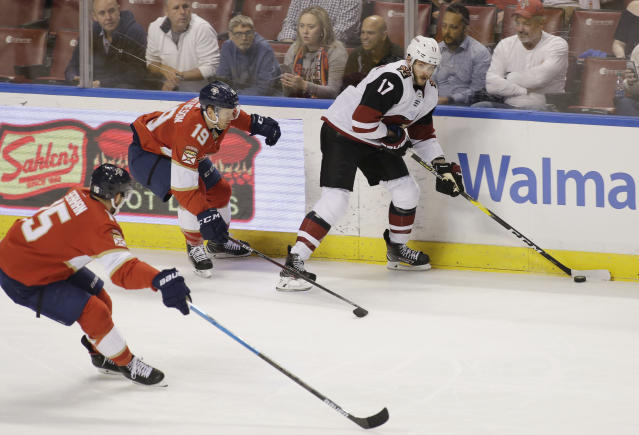 Florida Panthers center Riley Sheahan (15) and defenseman Mike Matheson (19) defend against Arizona Coyotes center Alex Galchenyuk (17) during the second period of an NHL hockey game on Thursday, March 21, 2019, in Sunrise, Fla. (AP Photo/Terry Renna)