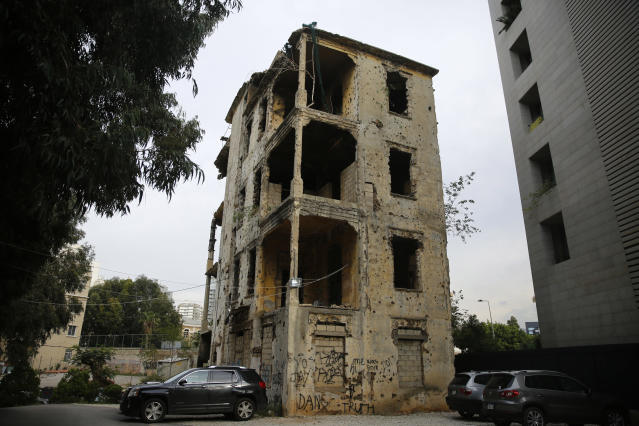 In this Dec. 2, 2018, photo, cars park in front of a building that is still riddled with bullets and shells on the former frontline of the 1975-1990 Lebanese civil war in Beirut, Lebanon. Nearly 30 years after civil war guns fell silent, dozens of bullet-scarred, shell-pocked buildings are still standing _ testimony to a brutal conflict that raged for 15 years and took the lives of 150,000 people. (AP Photo/Hassan Ammar)