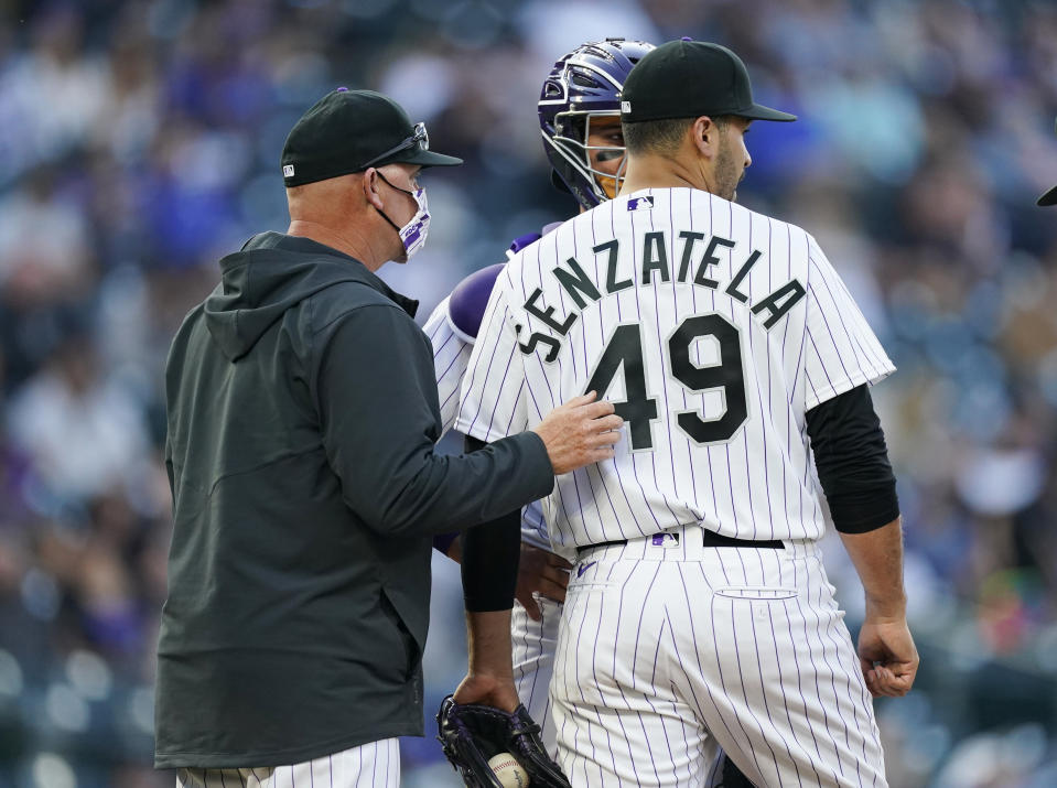 Colorado Rockies pitching coach Steve Foster, left, confers with starting pitcher Antonio Senzatela after Senzatela gave up an RBI-single to Los Angeles Dodgers' Will Smith in the first inning of a baseball game Friday, April 2, 2021, in Denver. (AP Photo/David Zalubowski)