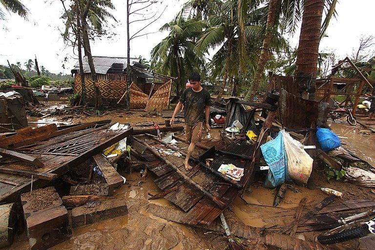 A resident walks amongst destroyed houses after Typhoon Bopha hit Compostela town, on the island of Mindanao