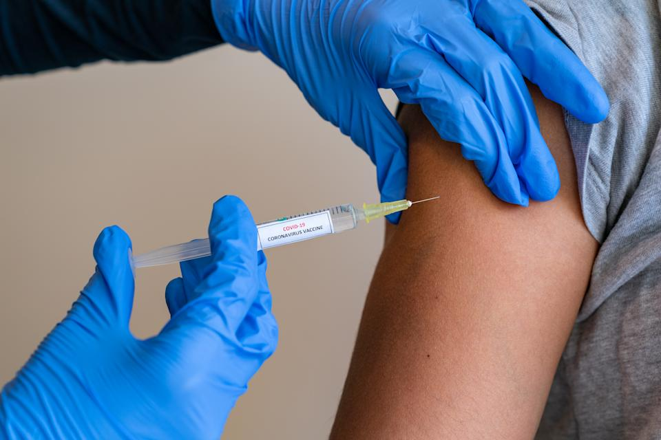 This picture depicts a young female clinician using a syringe to inject a concept COVD-19 liquid vaccine into a young girl patient during the Phase 3 vaccination human trials.