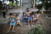Children eat free arepas or corn flour patties, given to them by Andres Burgos, a 55-year-old publicist, in Macuto, Venezuela, Saturday Oct. 24, 2020. Burgos, who is on a mission to feed the hungry, rode to the seaside city in Venezuela's La Guaira state, accompanied by other cyclists to distribute the arepas he made to needy children, adults and the elderly. (AP Photo/Ariana Cubillos)