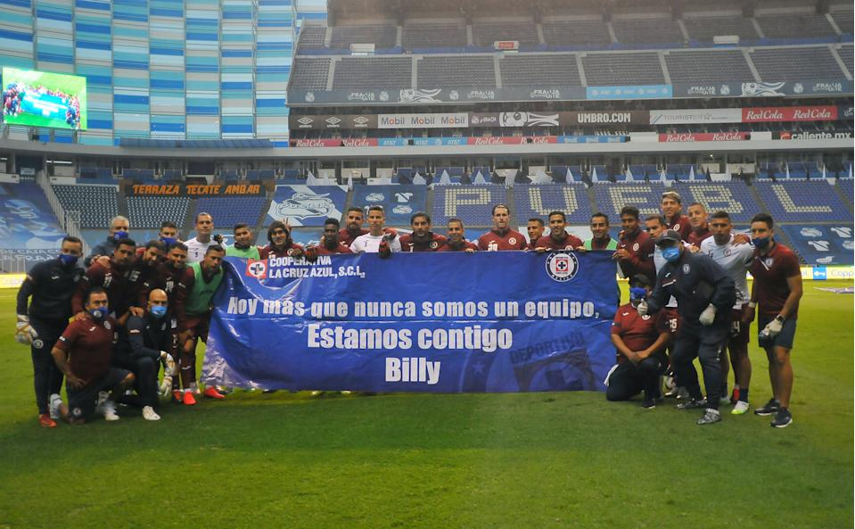 """Players of Cruz Azul show a banner to show their support to Guillermo """"Billy"""" Alvarez, the president of the club who is accused of money laundering and of links with the organized crime, before their Guardianes football tournament match against Puebla, at the Cuauhtemoc stadium in Puebla, Puebla State, Mexico, on July 31, 2020, amid the COVID-19 novel coronavirus pandemic. - The tournament is played without spectators as a preventive measure against the spread of COVID-19. (Photo by Victor CRUZ / AFP) (Photo by VICTOR CRUZ/AFP via Getty Images)"""
