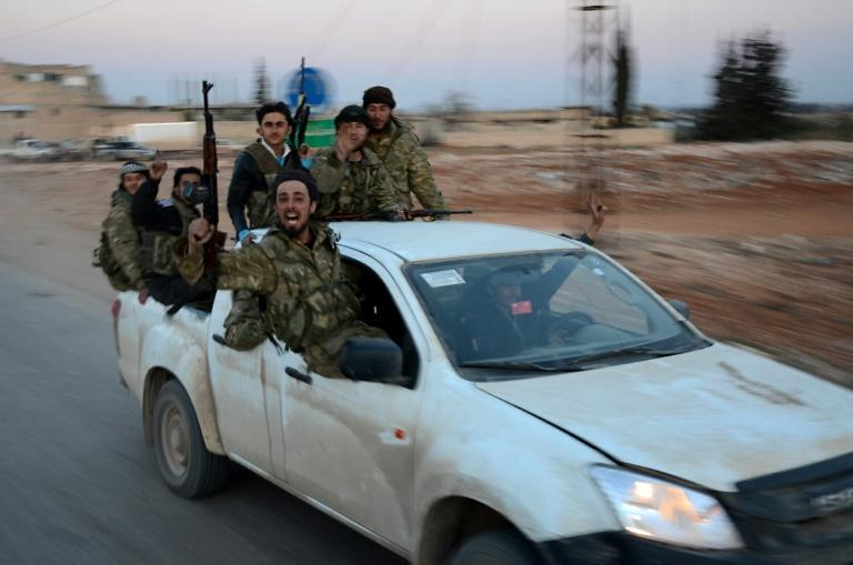 Turkish-backed Syrian rebels gesture as they drive in the northwestern border town of al-Bab on February 23, 2017 after capturing it from the Islamic State group