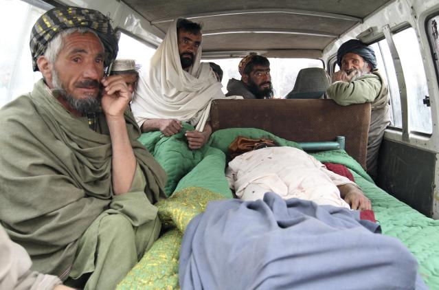 """Afghan men sit in a bus with the body of a person who was allegedly killed by a U.S. service member in Panjwai, Kandahar province south of Kabul, Afghanistan, Sunday, March 11, 2012. Afghan President Hamid Karzai says a U.S. service member has killed more than a dozen people in a shooting, including nine children and three women. Karzai called the attack Sunday """"an assassination"""" and demanded an explanation from the United States. He says several people were also wounded in the attack on two villages near a U.S. base in the southern province of Kandahar. (AP Photo/Allauddin Khan)"""