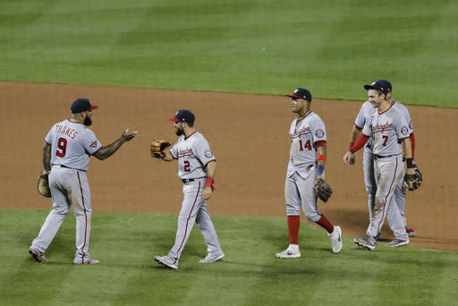 Washington Nationals' Eric Thames (9) and Adam Eaton (2) celebrate with teammates Starlin Castro (14) and Trea Turner (7) after a baseball game against the New York Mets Tuesday, Aug. 11, 2020, in New York. The Nationals won 2-1. (AP Photo/Frank Franklin II)