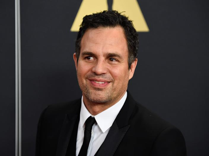 Mark Ruffalo at an event. He wears a black suit and tie.