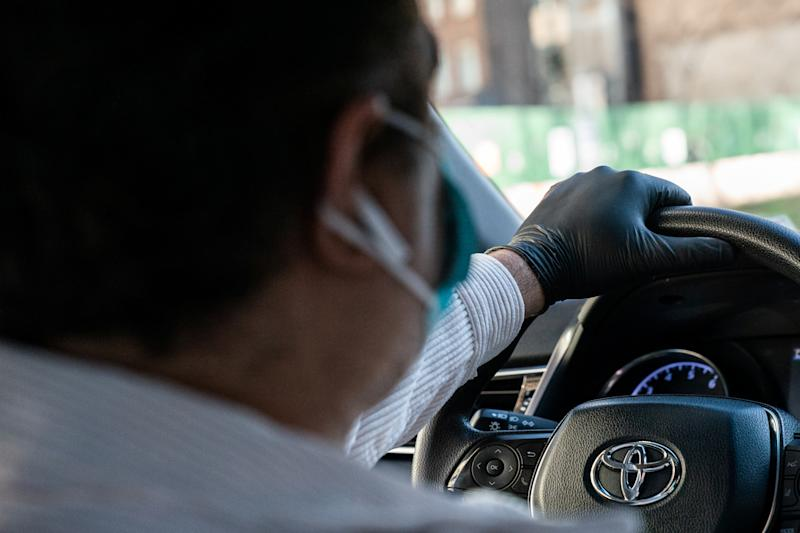 An Uber driver wearing a protective glove is seen in the Manhattan borough, following the outbreak of coronavirus disease (COVID-19), in New York City, U.S., March 15, 2020. REUTERS/Jeenah Moon