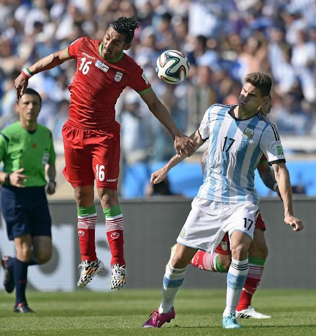 Iran's Reza Ghoochannejhad heads the ball past Argentina's Federico Fernandez during the group F World Cup soccer match between Argentina and Iran at the Mineirao Stadium in Belo Horizonte, Brazil, Saturday, June 21, 2014. (AP Photo/Martin Meissner)