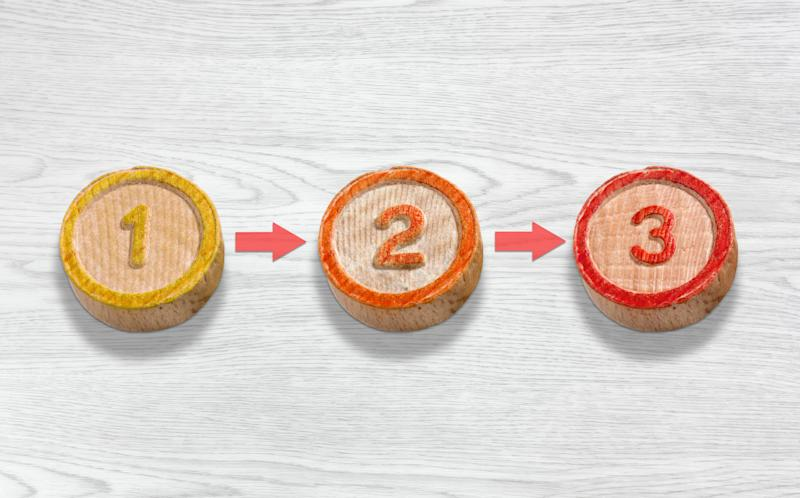 Three round wooden blocks numbered one, two, and three in a row.