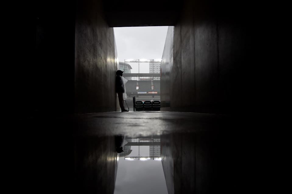 BALTIMORE, MD - MAY 12: An employee of Oriole Park at Camden Yards waits out the rain delay prior to the start of the game between the Baltimore Orioles and the Los Angeles Angels on May 12, 2019 in Baltimore, Maryland. (Photo by Will Newton/Getty Images)