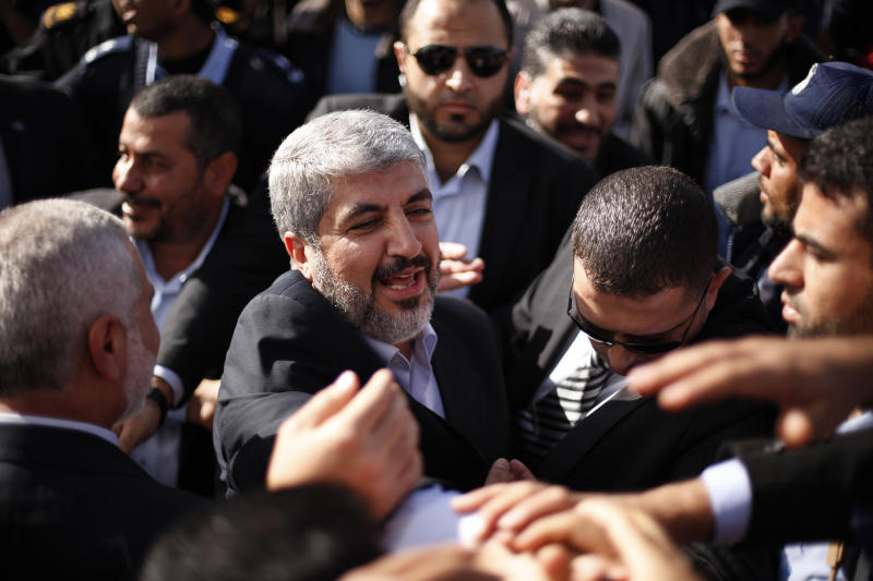 The exiled Hamas chief Khaled Mashaal shakes hands with supporters upon his arrival at Rafah crossing in the southern Gaza Strip, Friday, Dec. 7, 2012. The exiled Hamas chief broke into tears Friday as he arrived in the Gaza Strip for his first-ever visit, a landmark trip reflecting his militant group's growing international acceptance and its defiance of Israel. Khaled Mashaal, who left the West Bank as a child and leads the Islamic militant movement from Qatar, crossed the Egyptian border, kissed the ground, and was greeted by a crowd of Hamas officials and representatives of Hamas' rival Fatah party. He was also welcomed by a group of Palestinian orphans — children of Gaza militants killed by Israel in recent years — wearing military-style uniforms. (AP Photo/Suhaib Salem , Pool)