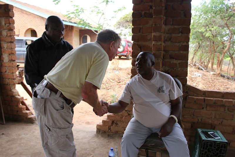 John Coyne shakes hands with a resident in Malawi. (Wells for Zoë/Flickr)
