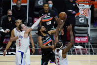 San Antonio Spurs guard Patty Mills (8) shoots next to Los Angeles Clippers forward Nicolas Batum (5) and forward Kawhi Leonard (2) during the fourth quarter of an NBA basketball game Tuesday, Jan. 5, 2021, in Los Angeles. (AP Photo/Ashley Landis)
