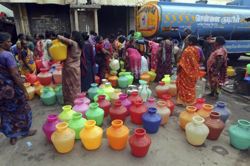 Indians wait to fill vessels filled with drinking water from a water tanker in Chennai, capital of the southern Indian state of Tamil Nadu, Wednesday, June 19, 2019. Millions of people are turning to water tank trucks in the state as house and hotel taps run dry in an acute water shortage caused by drying lakes and depleted groundwater. Some private companies have asked employees to work from home and several restaurants are closing early and even considering stopping lunch meals if the water scarcity aggravates. (AP Photo/R. Parthibhan)