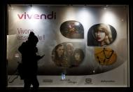 A woman walks pass by a sign of Vivendi at the main entrance of the entertainment-to-telecoms conglomerate headquarters in Paris
