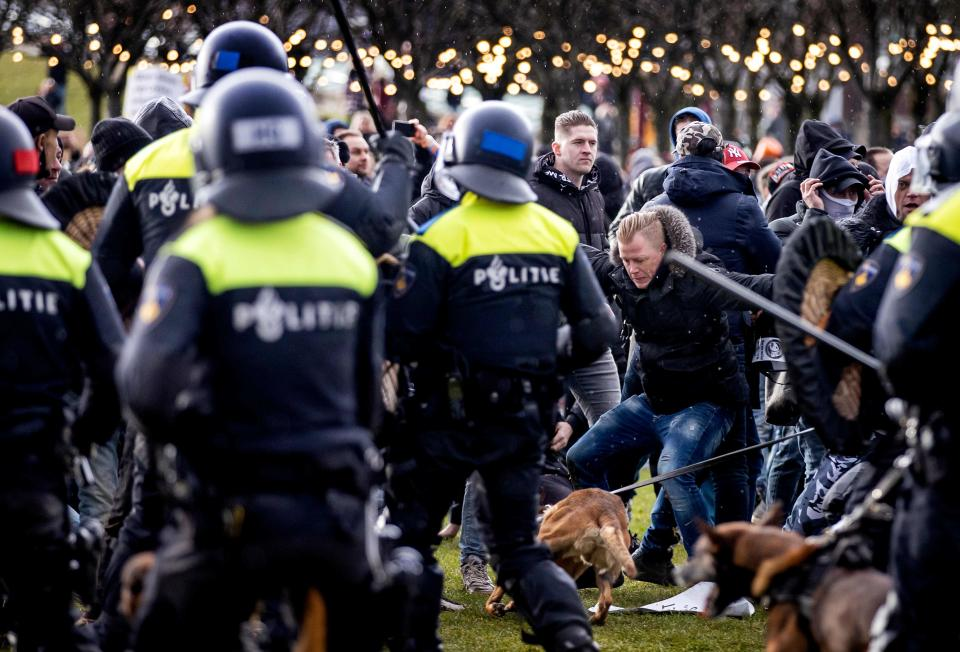<p>Demonstrators face Dutch police at the Museumplein, in Amsterdam, on January 17, 2021</p> (Photo by ROBIN VAN LONKHUIJSEN/ANP/AFP via Getty Images)