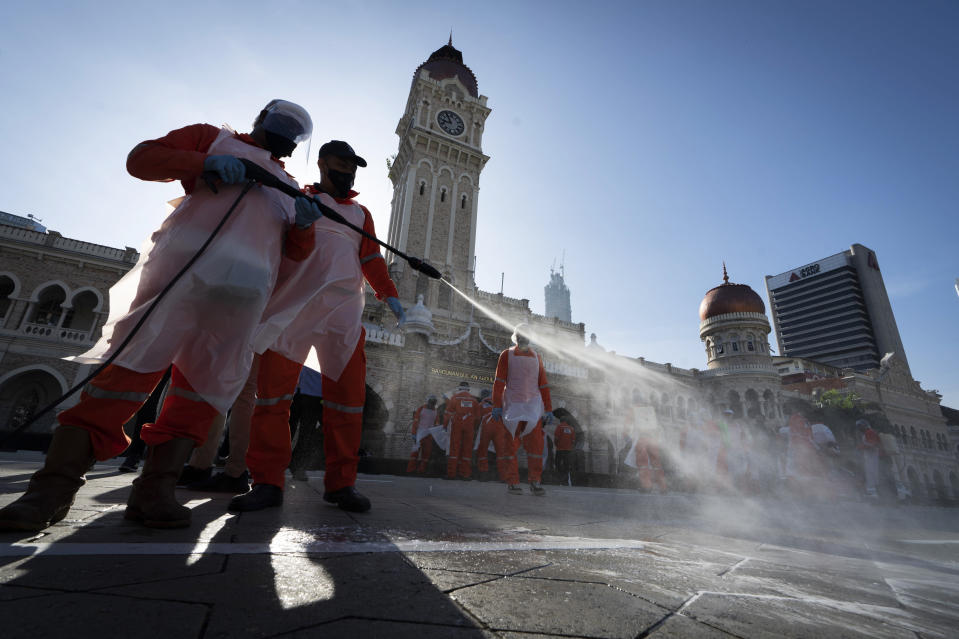 City hall workers spray a disinfectant Merdeka Square, or independence square, situated in front of the Sultan Abdul Samad Building, background, in Kuala Lumpur, Malaysia, Saturday, Oct. 17, 2020. Malaysia will restrict movements in its biggest city Kuala Lumpur, neighboring Selangor state and the administrative capital of Putrajaya from Wednesday in an attempt to curb a sharp rise in coronavirus cases. (AP Photo/Vincent Thian)