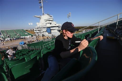 Jennifer Copelin, of Goose Creek, S.C., numbers seats on the basketball stadium installed on the flight deck of the USS Yorktown on Thursday, Nov. 8, 2012, in Charleston, S.C. The Carrier Classic off San Diego went so well last year that organizers expanded it this season and switched coasts. The Yorktown hosts two games on Friday, Notre Dame women face Ohio State, followed by the Buckeye's men against Marquette. (AP Photo/The Post And Courier, Tyrone Walker)