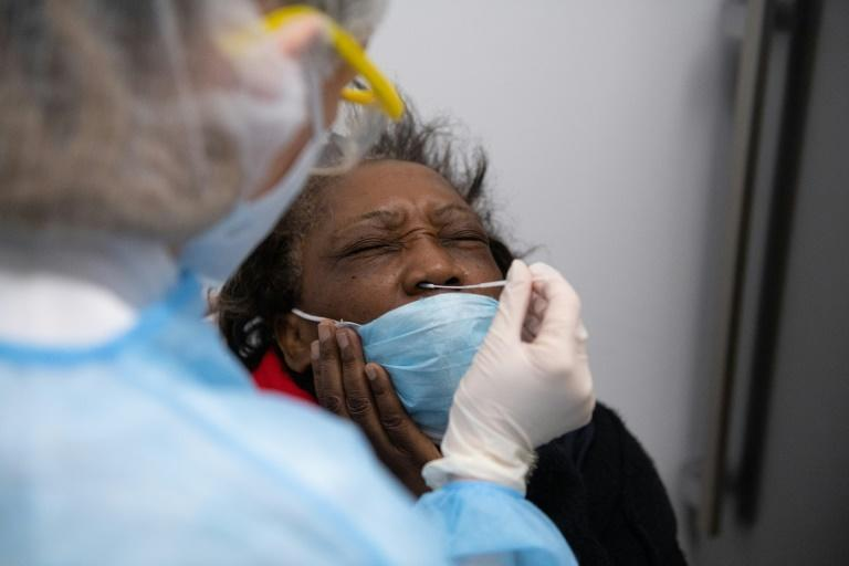 A French pharmacy employee carries out a swab test on a patient